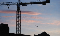 A plane flies past the Nolan Mains construction site in Edina.
