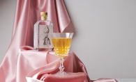 A bottle of Dampfwerk pear brandy sits alongside a glass on pink satin.