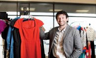 Clothes Mentor owner Dan Canfield holds a red dress.