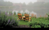 Two wooden chairs sit near the water in Centennial Lakes Park.