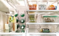 A fridge organized with clear, labeled bins for snacks, lunches, meal prep, veggies and fruit.