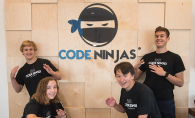 Four kids who learned coding through the Code Ninjas program pose in front of the logo.
