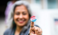 "A member of the League of Women Voters holds up an ""I Voted"" sticker."