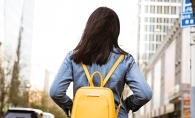 A woman wears a yellow backpack. Backpacks are a hot fall fashion trend, according to Wendy Witherspoon of Prink Style.
