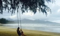 A woman sits on a swing on Klong Prao Beach