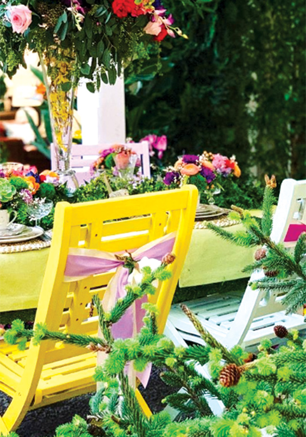 A pair of patio chairs sit by a flower display at the Galleria Garden Party.