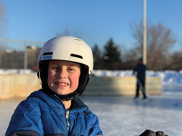 A young hockey player smiles for the camera.