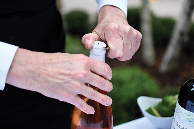 A server opens a bottle of champagne at the Mill City Summer Opera reception.