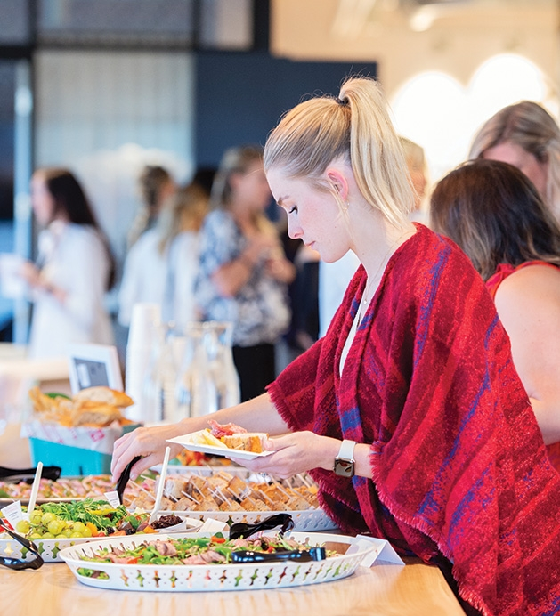 A guest puts food on her plate at the Evereve Minneapolis Influencer Social