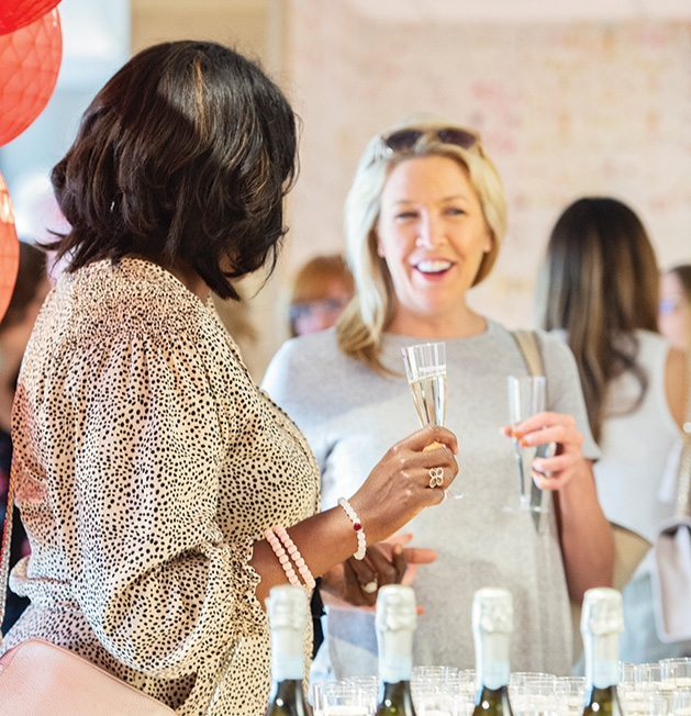 Two guests talk over champagne at the Evereve Minneapolis Influencer Social.