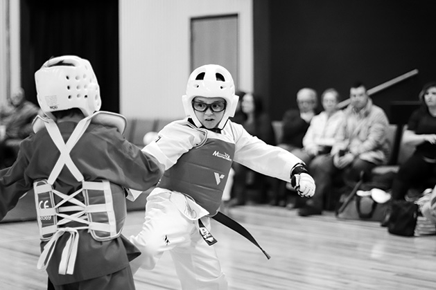 Two fencers face off in a black and white photo.