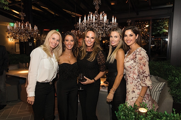A group of guests pose for a photo at the Restoration Hardware grand opening.