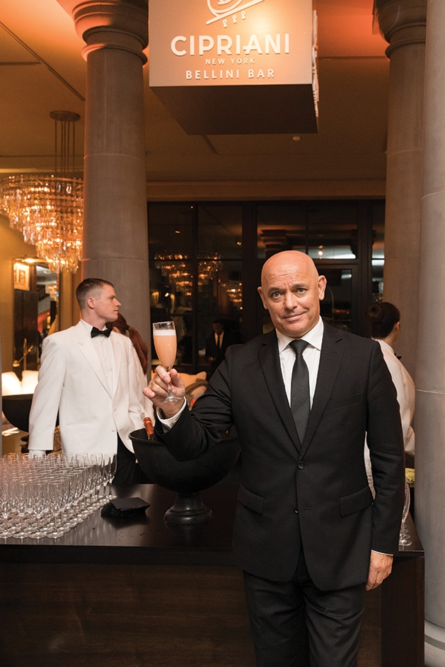 A man holds a glass of champagne at the Restoration Hardware Edina grand opening.