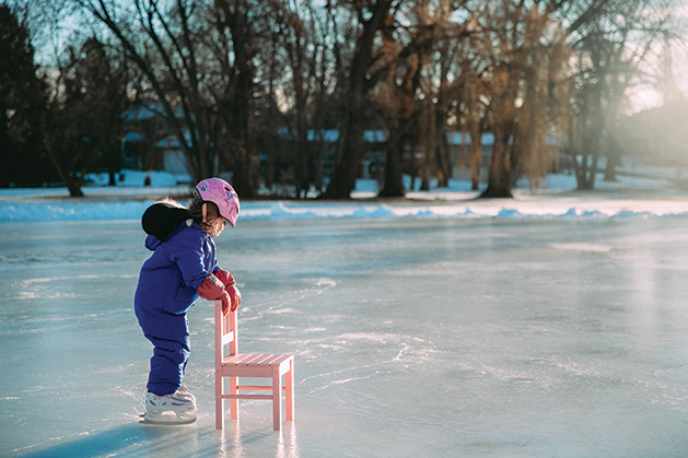 A young girl skates with the aid of a chair on a frozen Minnesota lake.