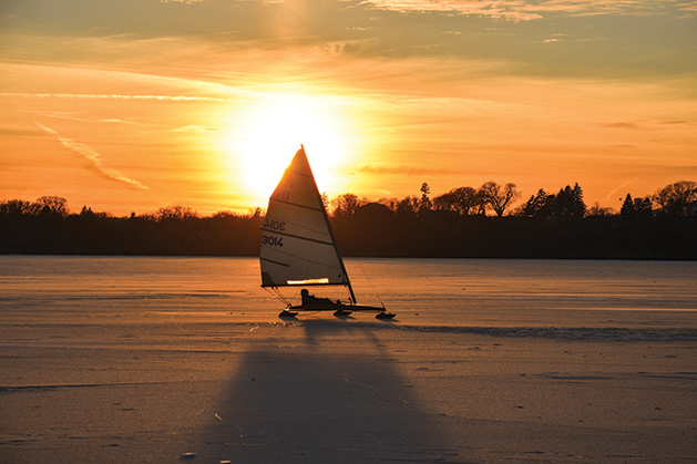 A boat sails on a Minnesota lake as the sun sets in the background.