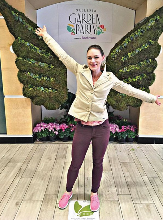 @vanillasparklekitty stands before a pair of floral wings at the Galleria Garden Party