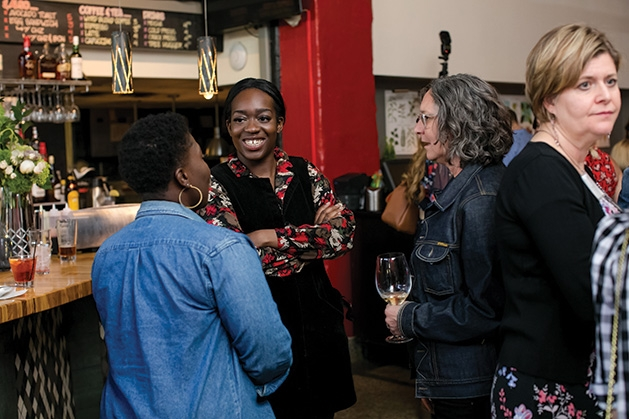 Attendees chat at the bar at the grand opening of The Riveter co-working space in Edina.