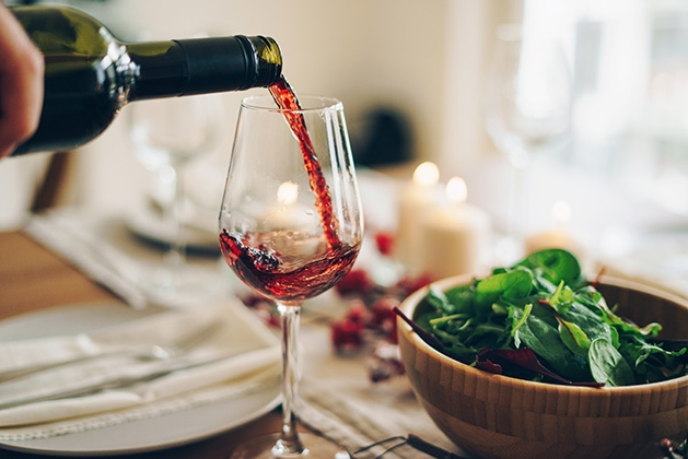 A glass of red wine is poured at a dinner table.