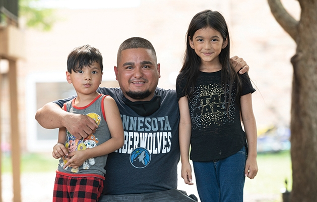 Man posing with two children.