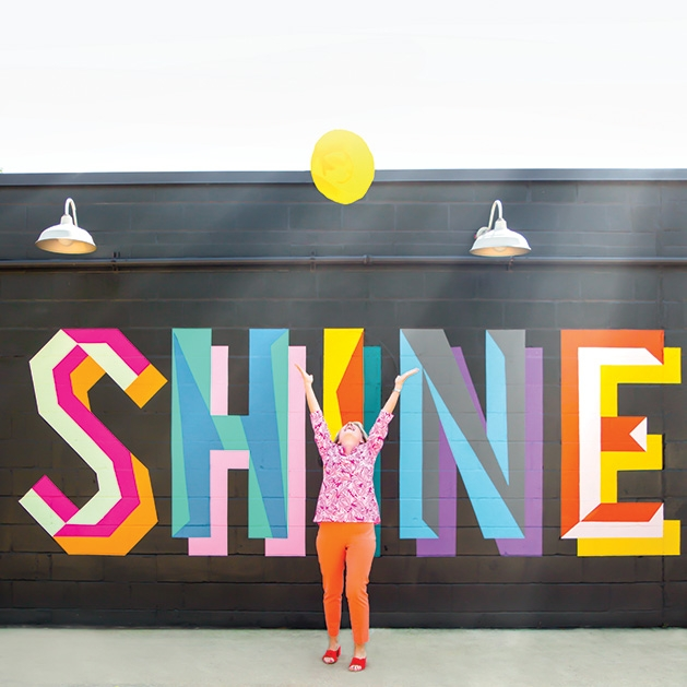"""A woman stands in front of a mural that reads """"SHINE"""" in a shot from See Them Shine"""