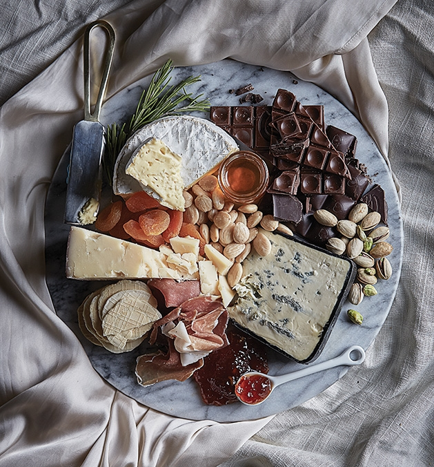 A plate full of various chocolates, cheese, fruits and snacks.