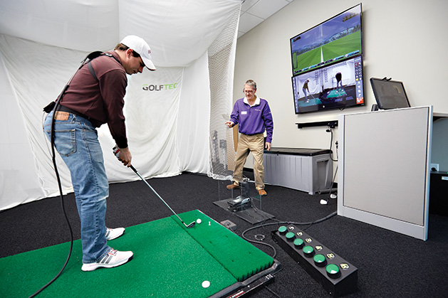 A golfer practices his swing at Golftec.