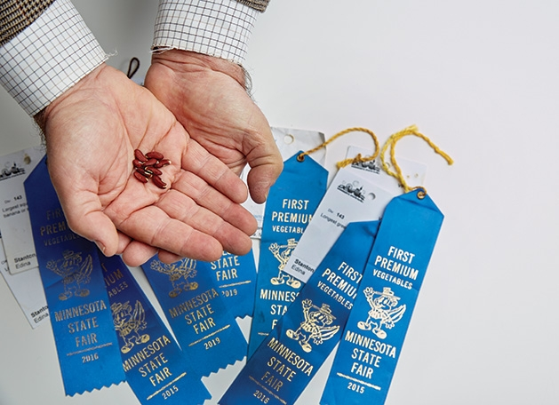 Russell Stanton holds seeds for his Minnesota State Fair blue ribbon-winning squash