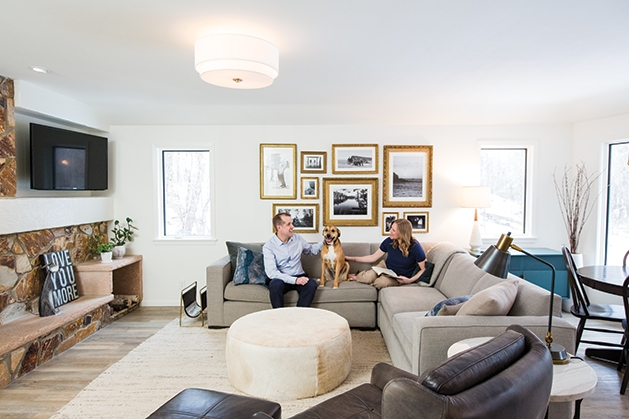 Jeff and Leslie Nicholson, founders of Quartersawn Design Build, sit with their dog in their remodeled home.