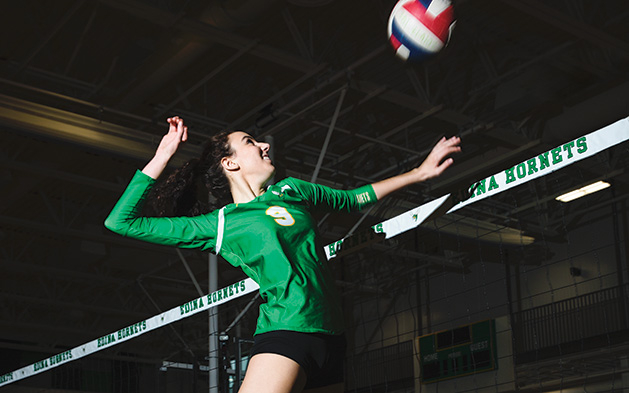 An athlete on the Edina High School volleyball team jumps for a spike.