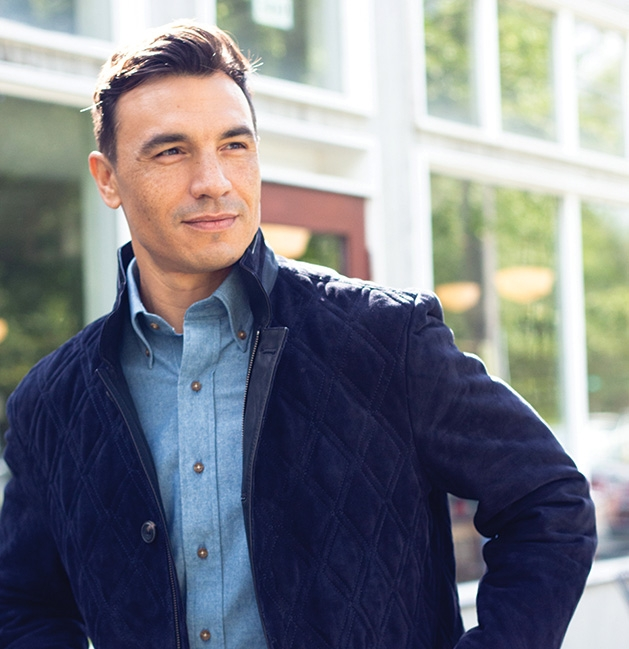 A man models a navy suede jacket blue chambray shirt from CircleRock