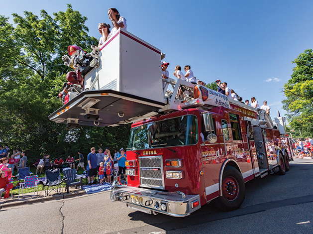 An Edina Fire Department truck rolls down the road as part of the Fourth of July parade.