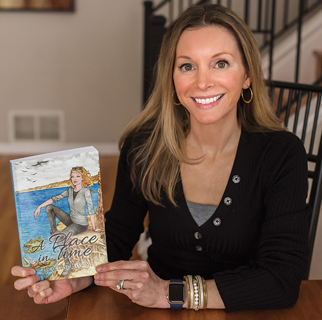 "Jacqueline Hanson holds a copy of her first novel, ""A Place in Time"""