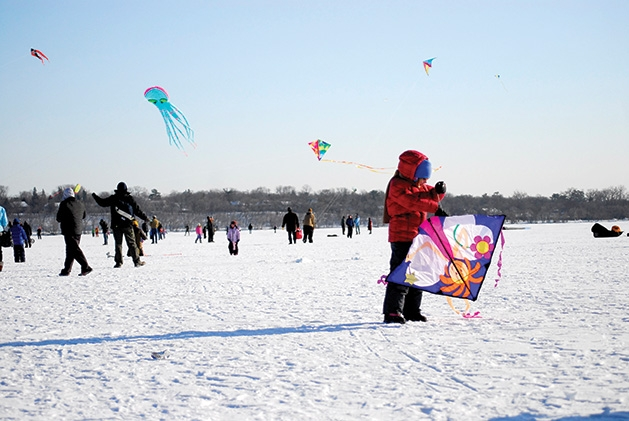 A child flies a kite at the Lake Harriet Kite Festival