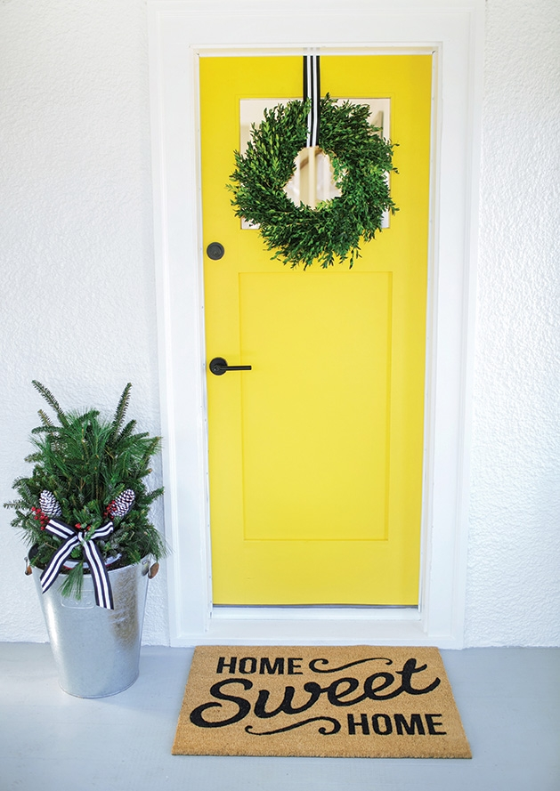 A yellow door decorated with a wreath on a home ready for a holiday sale.