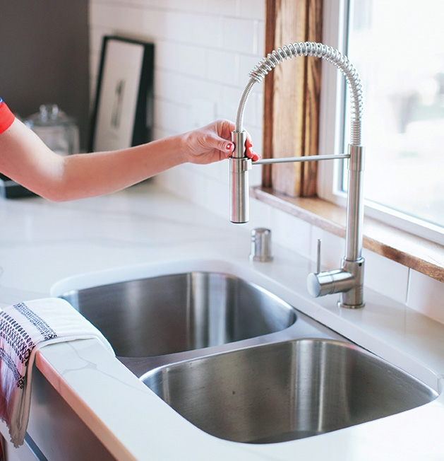 A home inspector checks out a faucet.