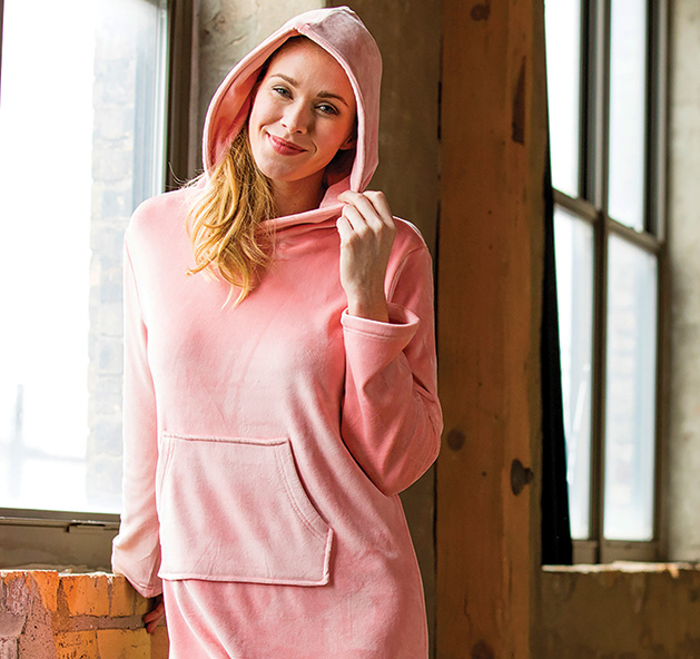 A woman wears a pink hooded snuggle lounger from Softie.