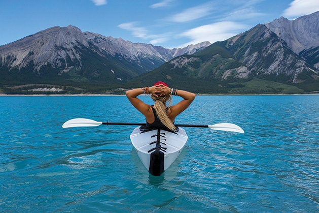 A woman in a kayak looks at some mountains ahead.