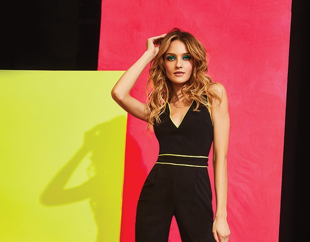 A woman models a black jumpsuit with neon yellow accents and shoes.
