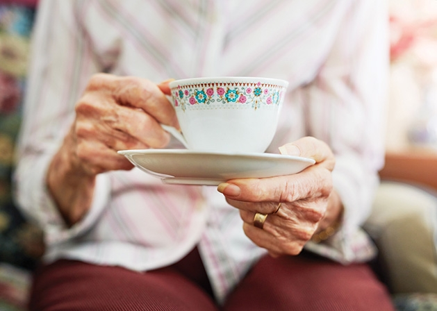 A woman drinks tea at a Memory Cafe event