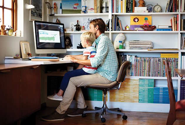 A father sits at an organized desk with his son.