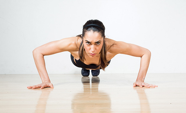 A woman prepares for a perfect push up.