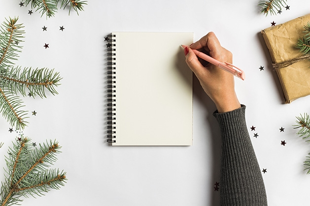 A person writes a to-do list to stay organized during the holidays.