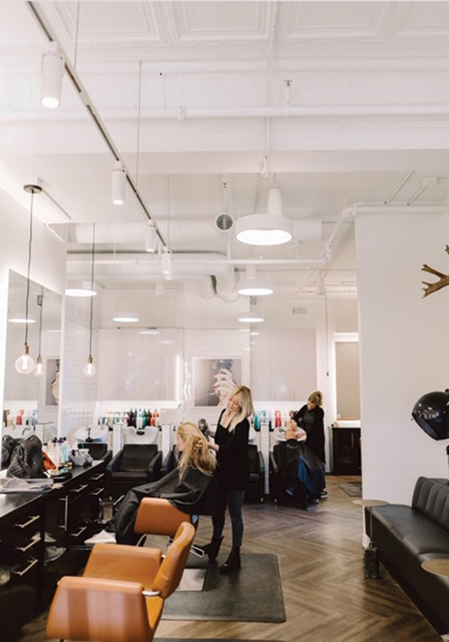 A hairstylist works on a customer's hair at Sloane's Beauty Bar.
