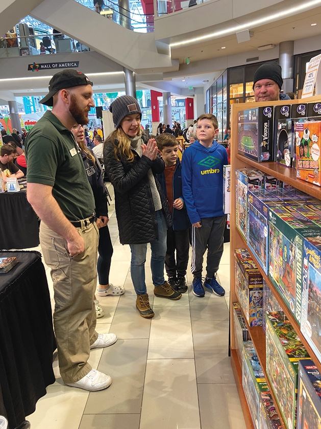 Shoppers explore products for family game night at Games by James' 40th anniversary celebration