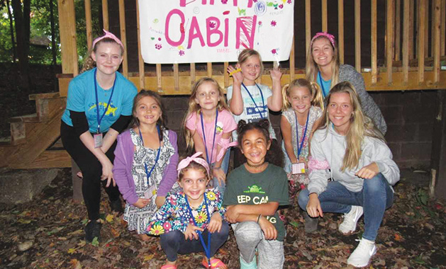"""Campers at Camp Erin pose in front of their """"Pink Cabin"""""""