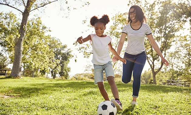Woman and daughter playing soccer in the park