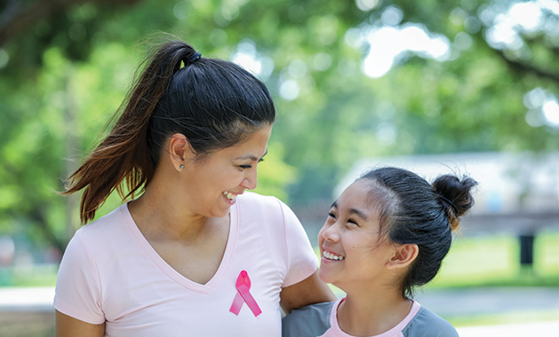 A mother and daughter wear pink breast cancer awareness shirts.