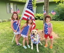 Kids decked out in patriotic clothing pose with the American flag and a dog.