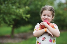A child holds apples at Apple Jack Orchards in Delano