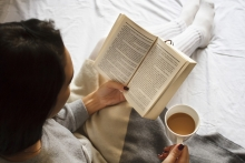 """A woman reads Erik Larson's """"The Splendid and the Vile"""" while drinking a cup of coffee."""